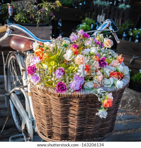 Vintage bicycle has beautiful colorful flowers in a basket on the front of the bike.