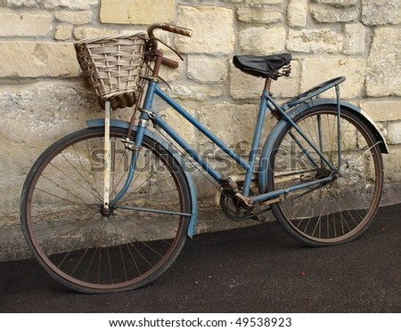 Vintage Bicycle Leaning against a Stone Wall - stock photo