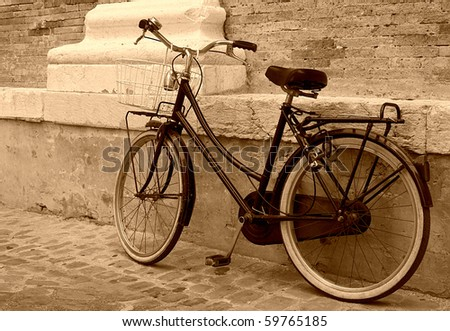 Vintage Bicycle leaning on a wall in italian street - stock photo