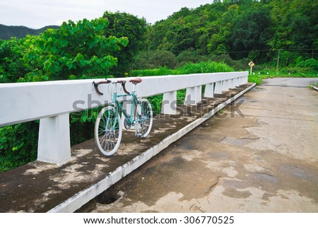 Vintage bicycle on a beautiful mountain road. - stock photo