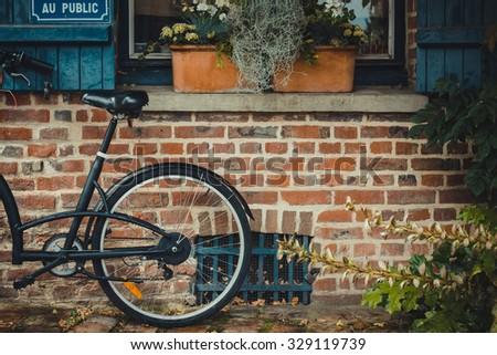 Vintage bicycle on vintage stone house wallb - stock photo