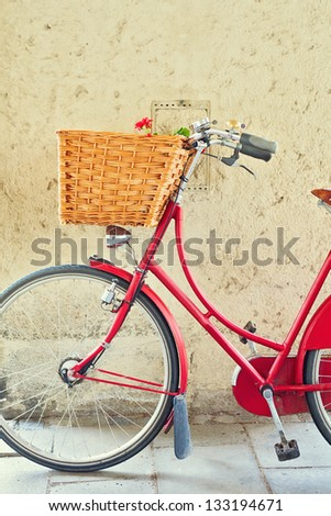 Vintage bicycle with basket over concrete wall - stock photo