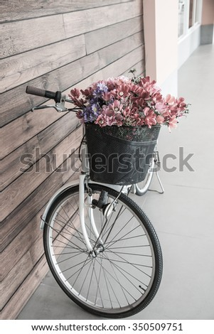 Vintage bicycle with flower in basket, Thailand. - stock photo