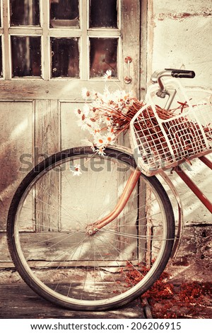 Vintage Bicycle with flowers  /summer background with bicycle (toned picture) - stock photo