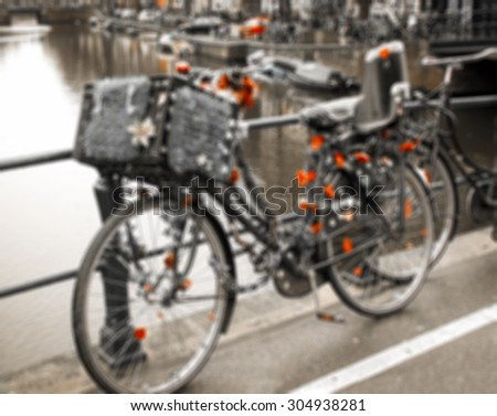 Vintage bike decorated with hearts and flowers on the bridge in Amsterdam (Netherlands). Blurred toned photo. - stock photo