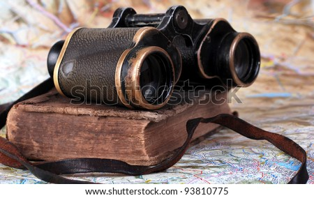 Vintage binocular with antique book at the topographic map background - stock photo