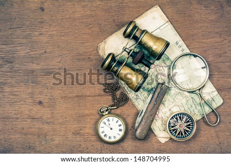 Vintage binoculars, compass, old map, magnifying glass, pocket watches, knife on wooden background - stock photo