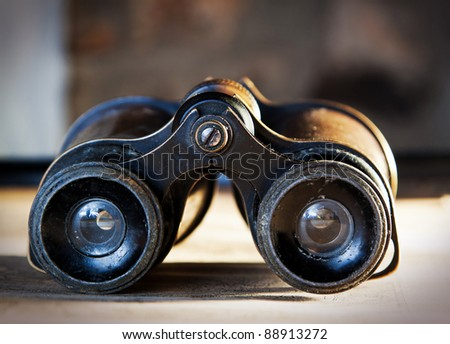 Vintage binoculars on an old map. - stock photo