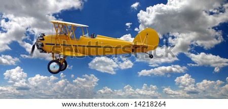 Vintage biplane over right clouds during a sunny day - stock photo