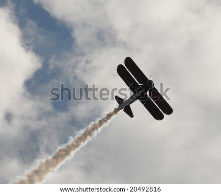 Vintage biplane performing an aerial stunt with smoke - stock photo