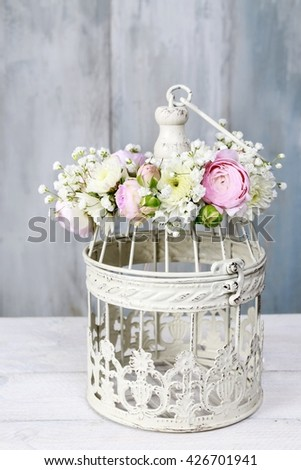Vintage bird cage decorated with wreath made of pink ranunculus flowers, tiny roses, chrysanthemums and gypsophila paniculata twigs. - stock photo