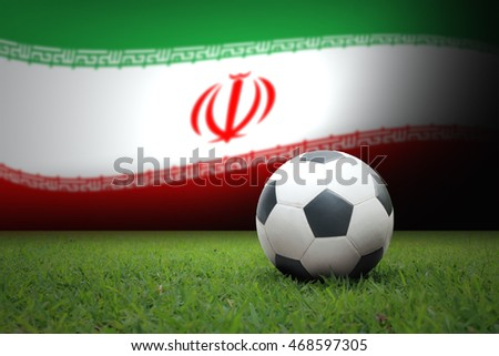 vintage black and white football ball on green grass has the national flag of Iran background