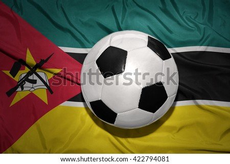 vintage black and white football ball on the national flag of mozambique - stock photo