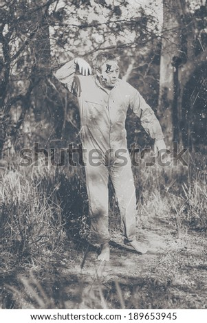 Vintage black and white horror photograph of a walking dead zombie wearing workers overalls starting a wave of terror when stumbling through country bushland  - stock photo