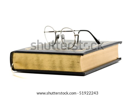 Vintage black book with glasses over white background - stock photo