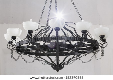 Vintage black chandelier with candles in room with white walls