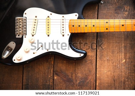 Vintage black double cutaway guitar on old wood surface.one piece maple neck. - stock photo
