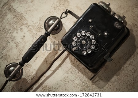 Vintage black phone hanging on old gray concrete wall - stock photo