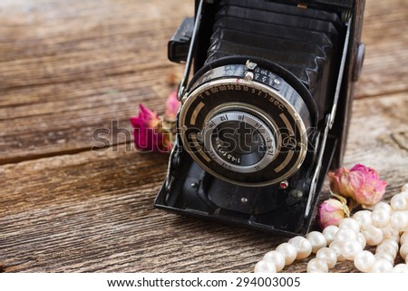 vintage black photo camera close up on wooden background - stock photo
