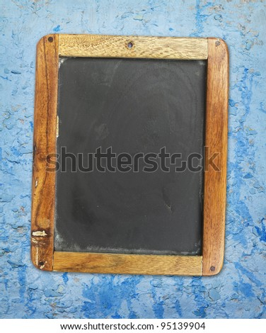 vintage blackboard on painted grungy wall, free copy space - stock photo