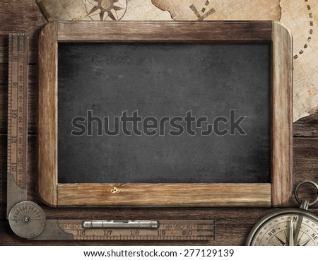 Vintage blackboard with treasure map, old compass and ruler. Adventure and discovery concept. - stock photo