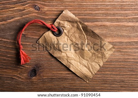 Vintage blank gift tag  on old wooden background. - stock photo