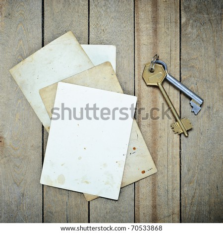 Vintage  blank photo paper and keys on a old wooden table - stock photo