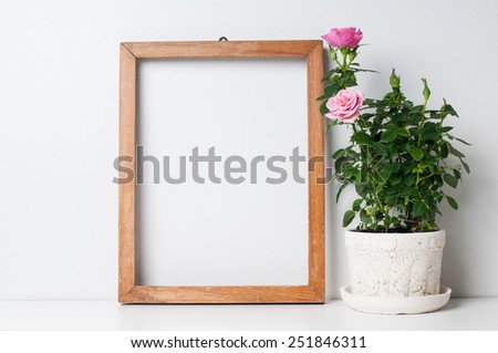 Vintage blank wooden frame and rose in a pot on a white wall - stock photo