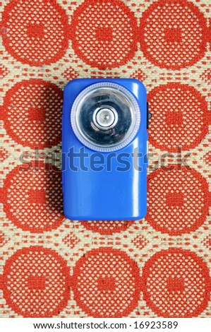 Vintage blue flashlight laying on the carpet - stock photo