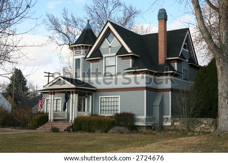 Vintage blue Victorian house with red and white trim and bare trees