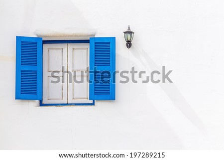 Vintage blue wood window on white wall - stock photo