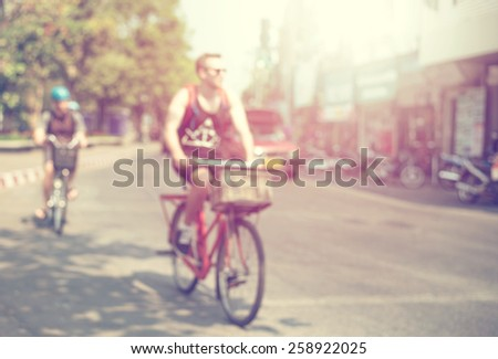 vintage blurred background, man driving bicycle on street in city - stock photo