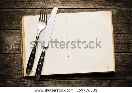 vintage book and cutlery on old wooden background - stock photo