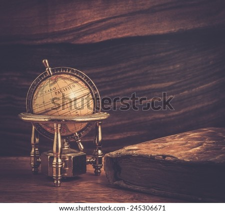 Vintage book and little globe on a wooden background  - stock photo