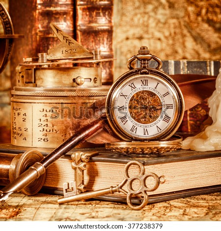 Vintage book, compass, telescope and a pocket watch lying on ancient world map in 1565. - stock photo