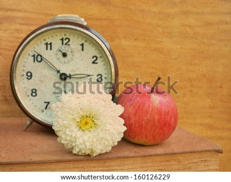 Vintage book with old clock and apple - stock photo