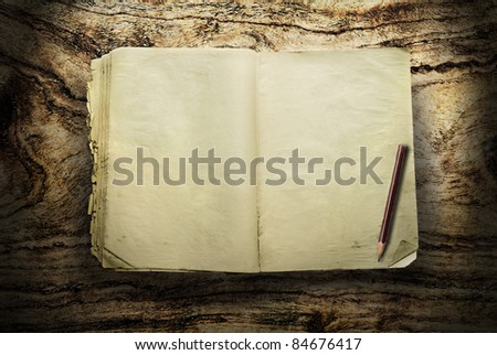 Vintage book with pencil on wood - stock photo
