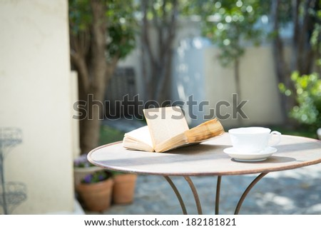 Vintage books and coffee cup on table - stock photo