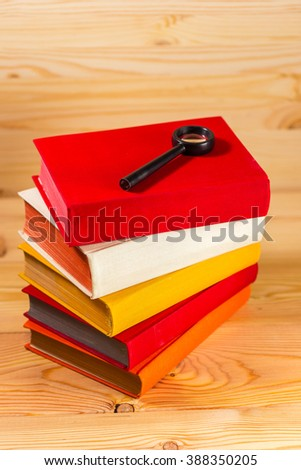 Vintage books and magnifying glass on wooden background.