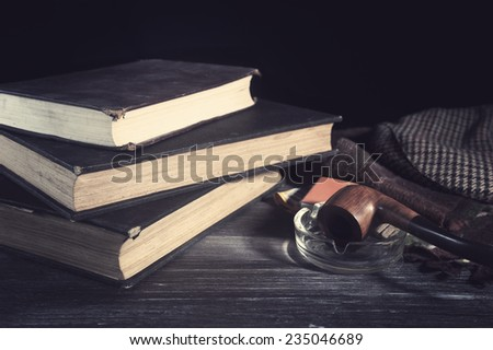 Vintage books and tobacco pipe on table - stock photo