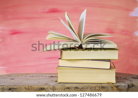 Vintage books arrangement on a old desk, one book open - stock photo