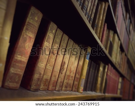 Vintage books in book case in library - stock photo