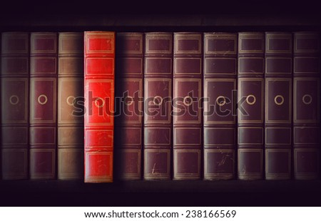 Vintage books in different shades of red and brown in bookcase, one book slightly pulled out - stock photo