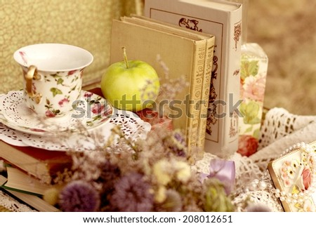 Vintage books with teacup and flowers - stock photo
