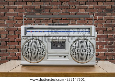 Vintage boombox on wood table with red brick wall. - stock photo