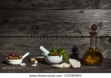 Vintage bottle of olive oil with bowls of olives, fresh basil and slices of bread on old wooden table