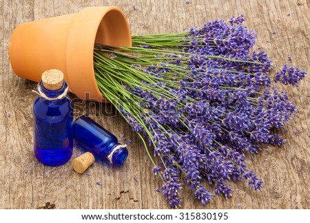 vintage bottles a bunch of lavender flowers in a ceramic pot - stock photo