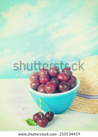 Vintage Bowl of Cherries against Cloudy Blue Sky Background with Straw Hat on Rustic White Painted Board Wood table.  Vertical with room or space for copy, text, your words.  Warm instagram process - stock photo