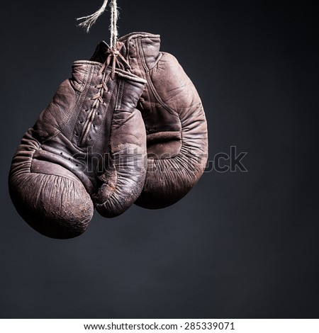 vintage boxing gloves on a  black background - stock photo