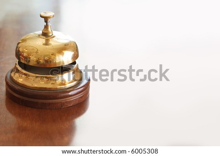 vintage brass bell on hotel bellstand - stock photo